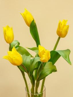 Buquê de tulipas amarelas com folhas verdes no fundo amarelo.