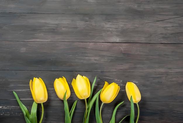 Buquê de tulipas amarelas com uma fita amarela em uma madeira