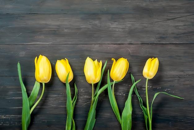 Buquê de tulipas amarelas com uma fita amarela sobre um fundo de madeira