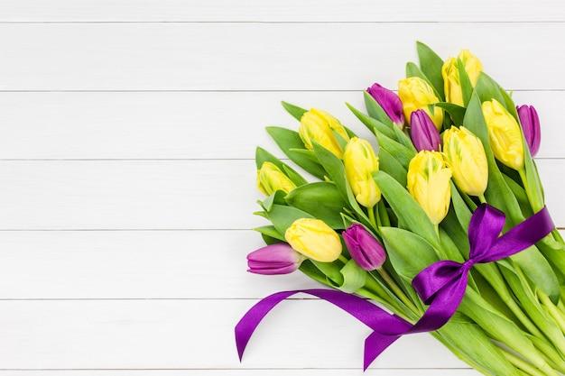Buquê de tulipas amarelas e rosa com fita roxa em fundo branco de madeira.