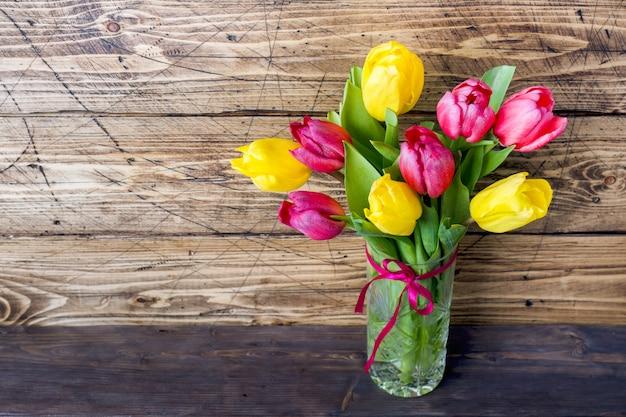 Buquê de tulipas amarelas e rosa em um de madeira.