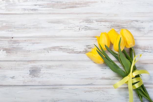 Buquê de tulipas amarelas e um presente com uma fita amarela sobre um fundo de madeira
