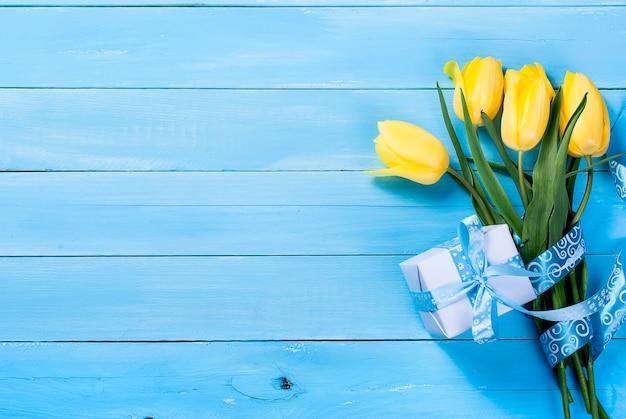 Buquê de tulipas amarelas e um presente com uma fita azul sobre um fundo azul de madeira