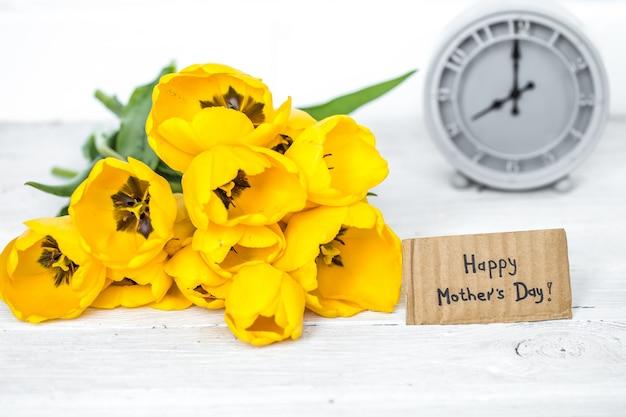 Buquê de tulipas amarelas e um relógio retrô em um fundo de madeira brilhante, espaço para texto, conceito de feriado