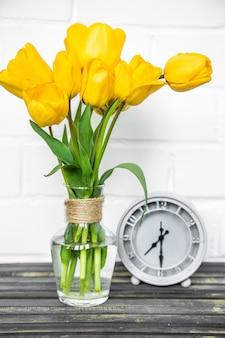 Buquê de tulipas amarelas e um relógio retrô