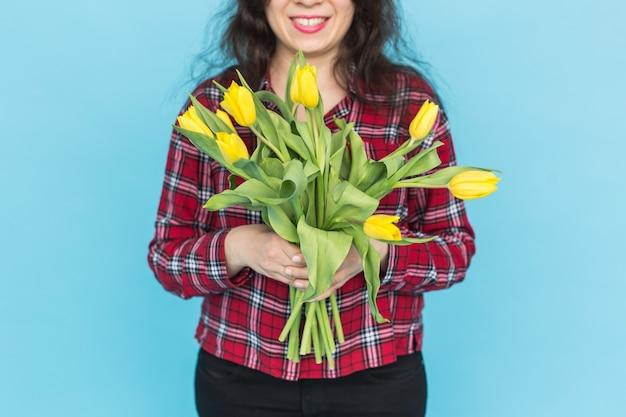 Buquê de tulipas amarelas nas mãos de uma mulher na parede azul