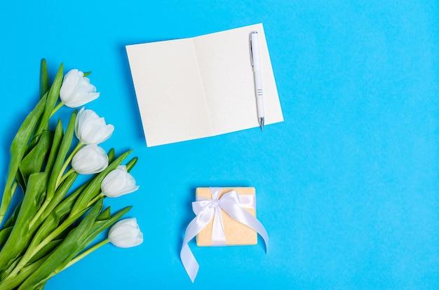 Buquê de tulipas brancas com caixa de presente, cartão e caneta na mesa azul clara. postura plana, espaço de cópia, conceito de primavera, lugar para texto, vista superior.