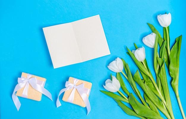 Buquê de tulipas brancas com cartão e caixas de presente em uma mesa azul. conceito de primavera, flat lay, copie o espaço. bandeira. vista de cima.