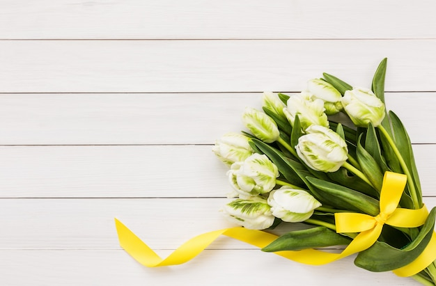 Buquê de tulipas brancas decoradas com uma fita amarela em um fundo de madeira branco, vista superior, espaço de cópia