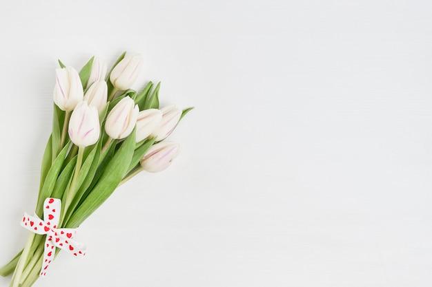 Buquê de tulipas brancas decorado com fita de corações em fundo branco de madeira