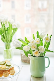 Buquê de tulipas brancas frescas em vaso e bolo com frutas cítricas
