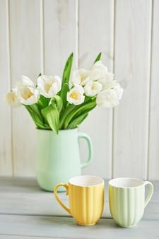 Buquê de tulipas brancas frescas em vaso e duas canecas