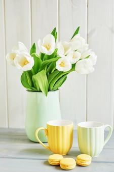 Buquê de tulipas brancas frescas em vaso, macarons de limão e duas canecas