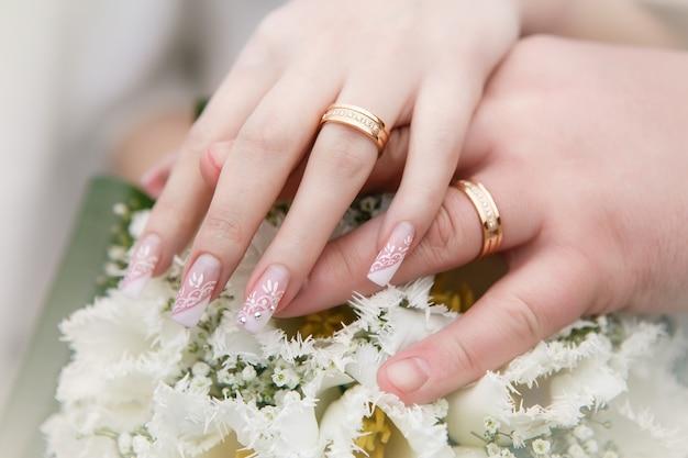 Buquê de tulipas brancas, mãos do noivo e da noiva com alianças de ouro close-up. conceito de casamento.