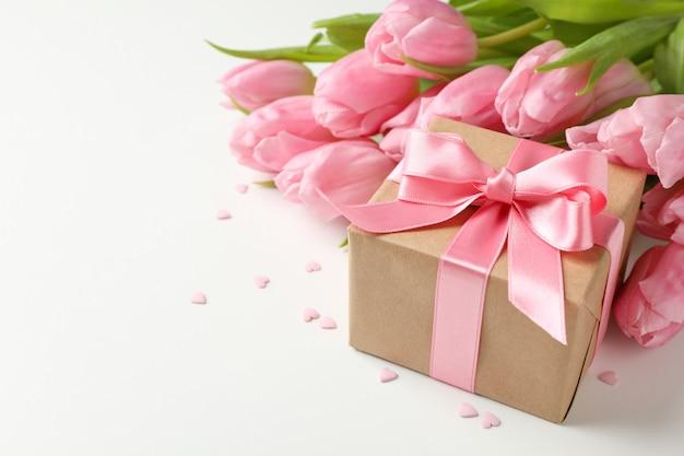 Buquê de tulipas, caixa de presente e pequenas corações em fundo branco, espaço para texto