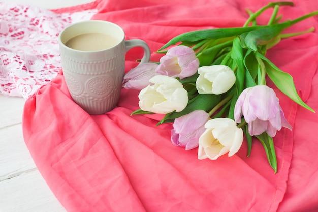 Buquê de tulipas com uma caneca de café e um presente em uma caixa vermelha em um pano-de-rosa