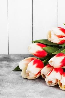 Buquê de tulipas cor de rosa brancas sobre um fundo cinza. copie o espaço