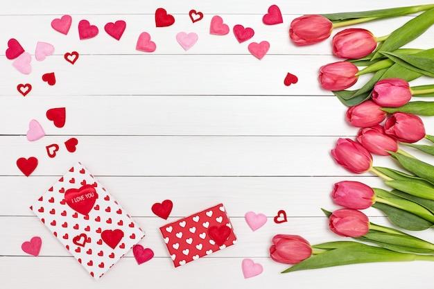 Buquê de tulipas cor de rosa, caixas de presente e corações em fundo branco.