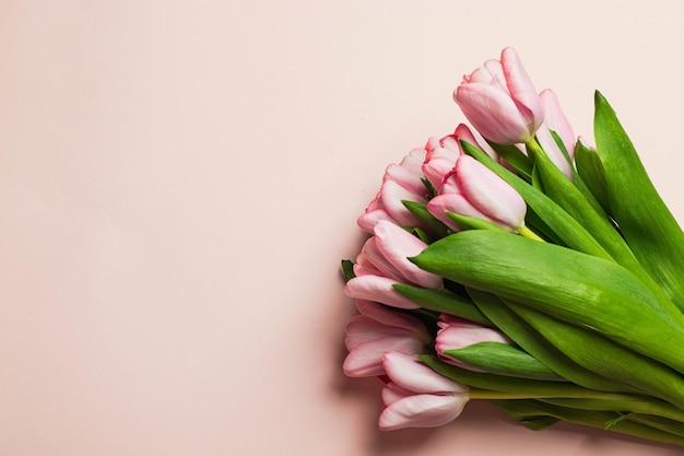 Buquê de tulipas cor de rosa com confetes em fundo rosa. vista superior com copyspace. conceito de cartão