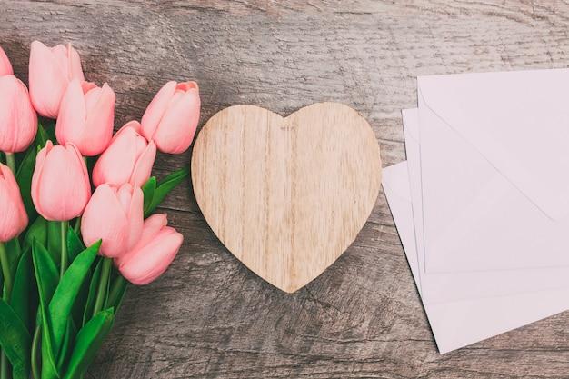 Buquê de tulipas cor de rosa e envelopes em branco brancos, sobre fundo de madeira