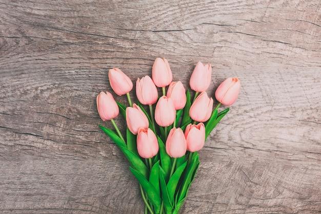Buquê de tulipas cor de rosa em fundo de madeira