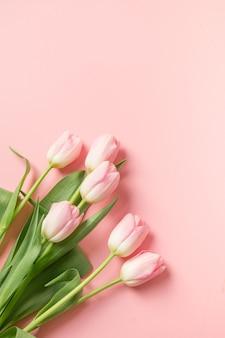 Buquê de tulipas cor de rosa em fundo rosa com espaço de cópia.