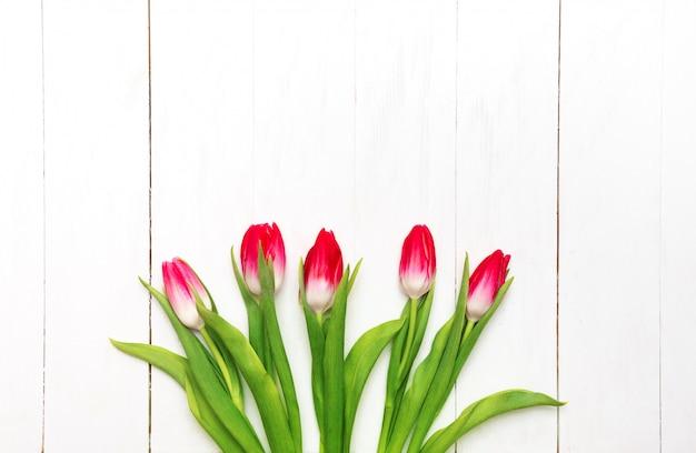 Buquê de tulipas cor de rosa em um fundo branco de madeira rústico