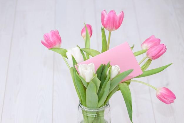 Buquê de tulipas cor de rosa em um vaso de vidro na superfície de madeira branca com cartão. superfície de primavera, férias, conceito de aniversário.