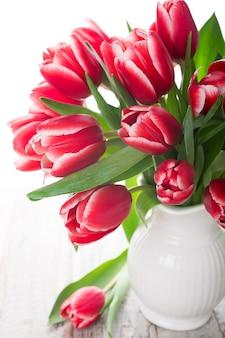 Buquê de tulipas cor de rosa em um vaso no fundo branco