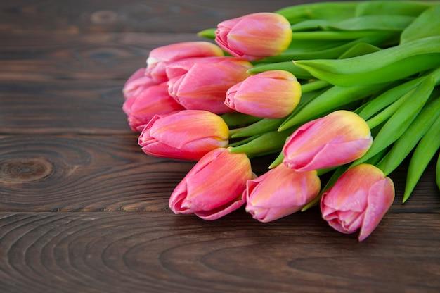 Buquê de tulipas cor de rosa em uma superfície de madeira