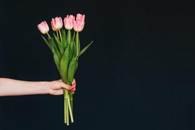 Buquê de tulipas cor de rosa na mão da menina em fundo preto