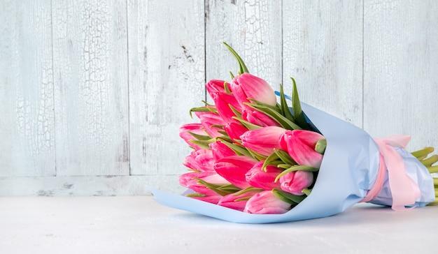 Buquê de tulipas cor de rosa na mesa de madeira