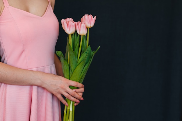 Buquê de tulipas cor de rosa nas mãos das mulheres