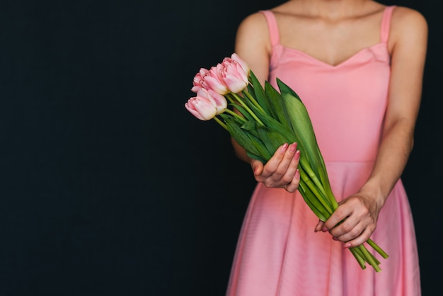 Buquê de tulipas cor de rosa nas mãos de uma menina em um vestido