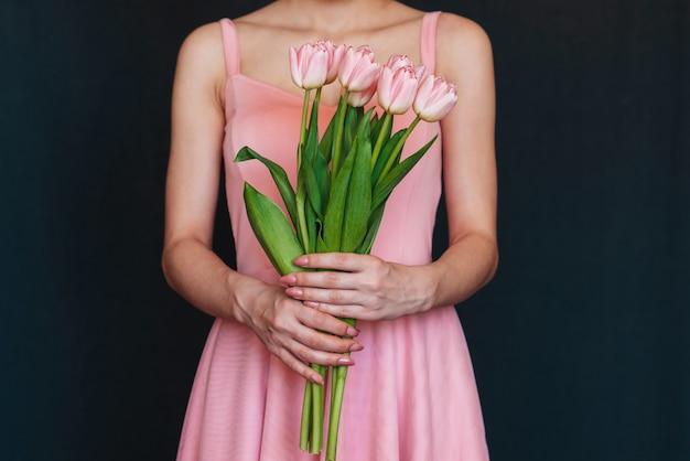 Buquê de tulipas cor de rosa nas mãos de uma menina