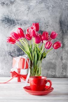 Buquê de tulipas cor de rosa, xícara de café e presente.
