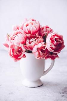 Buquê de tulipas da primavera em um vaso no fundo chique gasto