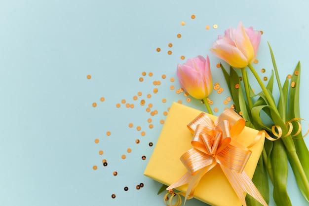 Buquê de tulipas delicadas e um presente de caixa amarela com um laço brilhante sobre um fundo azul isolado