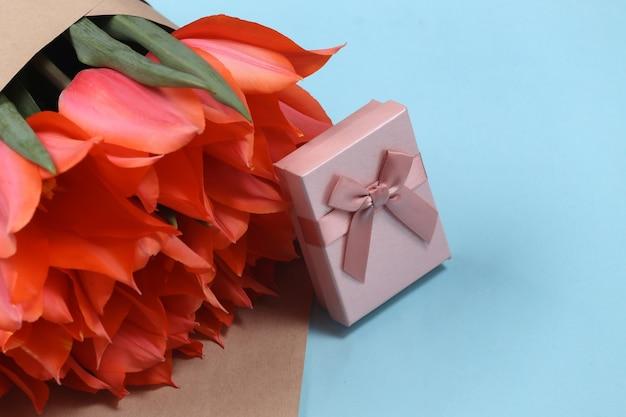 Buquê de tulipas e caixa de presente em fundo azul. dia das mães no feriado ou dia 8 de março, aniversário.
