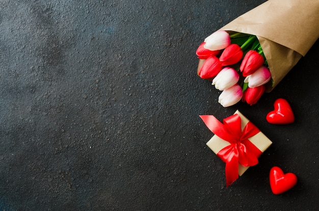 Buquê de tulipas e caixa de presente em fundo escuro.
