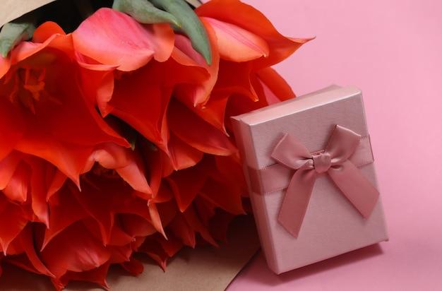 Buquê de tulipas e caixa de presente em fundo rosa. dia das mães no feriado ou dia 8 de março, aniversário.