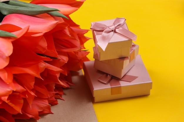 Buquê de tulipas e caixas de presente em fundo amarelo. dia das mães no feriado ou dia 8 de março, aniversário.