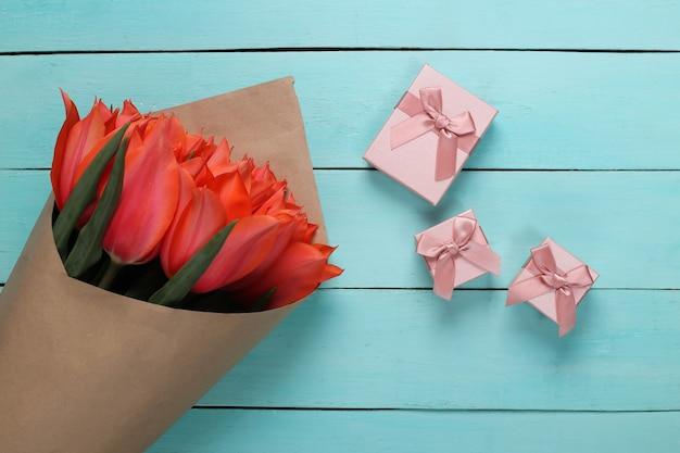 Buquê de tulipas e caixas de presente em fundo azul de madeira. dia das mães no feriado ou dia 8 de março, aniversário. vista do topo