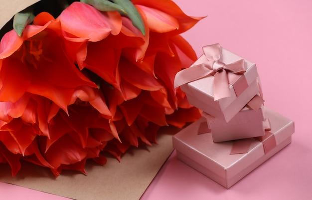 Buquê de tulipas e caixas de presente em fundo rosa. dia das mães no feriado ou dia 8 de março, aniversário.