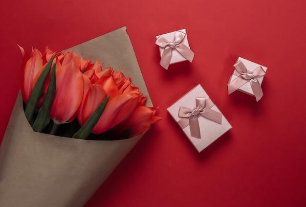 Buquê de tulipas e caixas de presente em fundo vermelho. dia das mães no feriado ou dia 8 de março, aniversário. vista do topo