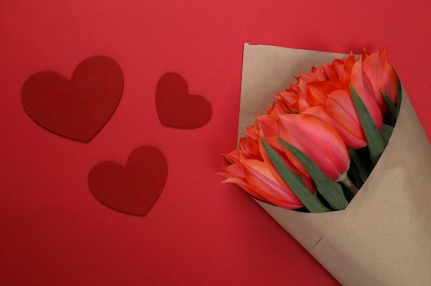 Buquê de tulipas e corações em fundo vermelho. feriado do dia das mães, 8 de março, aniversário ou dia dos namorados, pedido de casamento. vista do topo