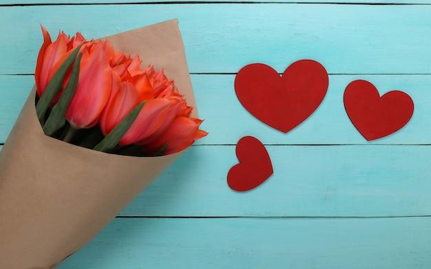 Buquê de tulipas e corações sobre fundo azul de madeira. feriado do dia das mães, 8 de março, aniversário ou dia dos namorados, pedido de casamento. vista do topo