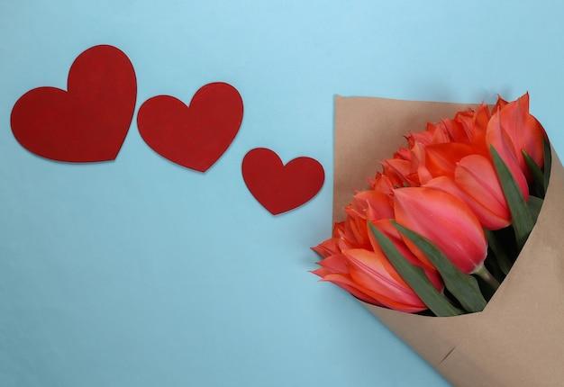 Buquê de tulipas e corações sobre fundo azul. feriado do dia das mães, 8 de março, aniversário ou dia dos namorados, pedido de casamento. vista do topo