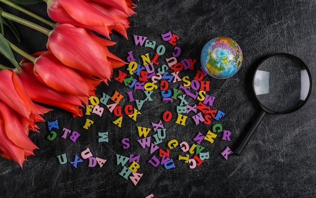 Buquê de tulipas e material escolar, cartas no quadro de giz. dia do conhecimento, de volta às aulas. vista do topo