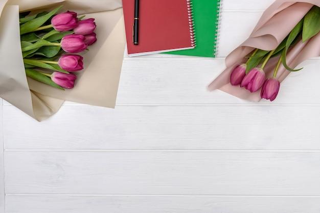Buquê de tulipas e um bloco de notas em branco na mesa de madeira